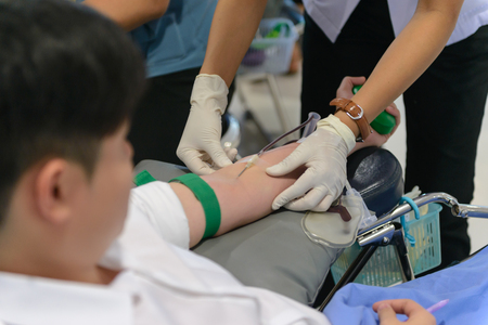 transfused: Nurse giving an intravenous injection to blood donor at blood donation Stock Photo
