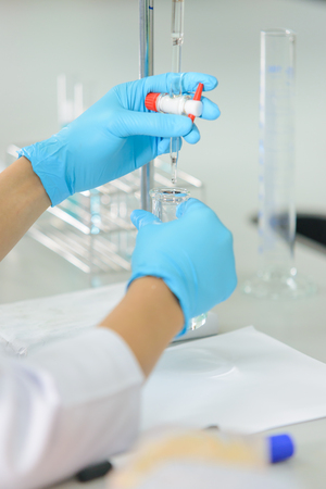 bureta: La mujer que es el científico es demostrar la técnica de valoración en el laboratorio Foto de archivo