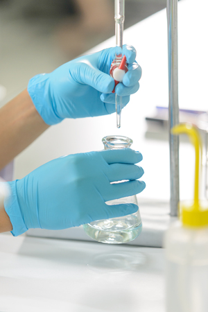 The woman who's the scientist is demonstrate the titration technique in the laboratory Stock Photo