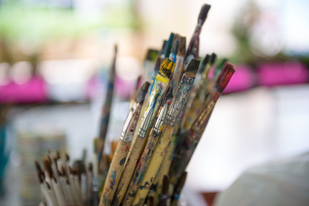 paintbrushes: artist paintbrushes in dirty bucket.