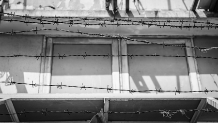 intrusion: abstract barbed wire fence lack and white shot Stock Photo