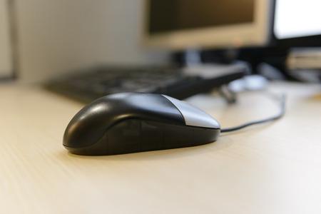 compute: Closeup computer mouse before computer desktop on brown wooden desk, entertainment or business concept Stock Photo