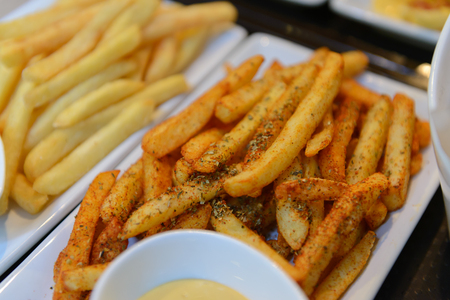 Spicy french fries in a white bowl Stock Photo