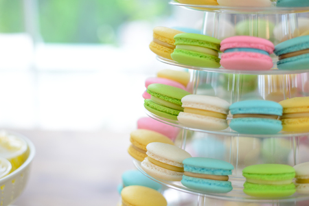 Close-up colorful macarons on pyramid-shaped plastic stand at party