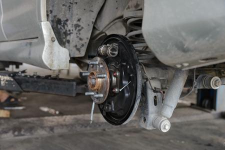 dirty car: Car brake repairing on scissor cranes lift in garage Stock Photo