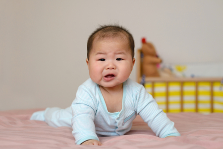 Portrait of asian baby  boy little 7 months old. wear a cap on the bed in his room