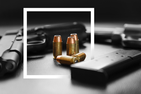 White paper frame with .45 Caliber hollow point bullets near handgun and magazine on leather furniture Stock Photo