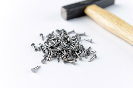Scattering small iron nails  with hammer isolated on white background, close-up view