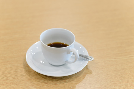 cup of hot coffee and spoon on wooden table in meeting room - coffee break