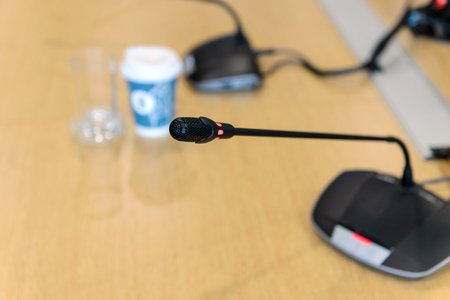 Selective focus conference microphones on the table in empty meeting room Stock Photo