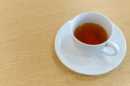 cup of hot tea and spoon on wooden table in meeting room