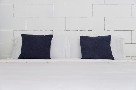 stacking of blue backrest pillow and white pillow on bed and white brick wall, interior modern bedroom