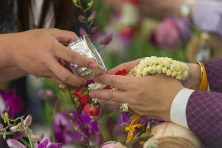 young peoples pouring  water and flowers on the hands of senior in Songkran ceremony, Thai New Year