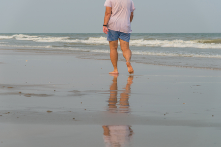 Man walking alone on the beach. beach travel at summer time concept