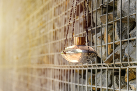 kerosene lamp hanging with gabion rock wall on background