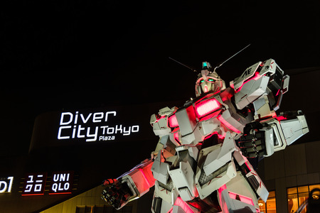 Tokyo, Japan - July 2018: Real-size of the Unicorn Gundam RX-0 standing in front of the Diver City Tokyo Plaza building is landmark of Odaiba, Tokyo, JAPAN - At Night time