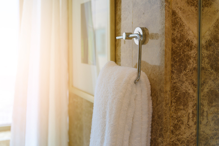 Close up clean white towel hanging on towel bar in bathroom prepared to use 스톡 콘텐츠