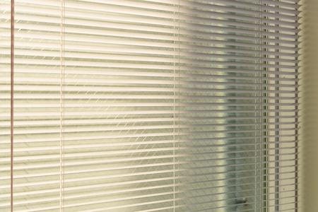 Aluminiumjalousien mit Sonnenlicht aus einem Fenster. Dekoration Interieur