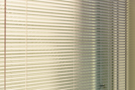 aluminum venetian blinds with sunlight coming from a window. decoration interior