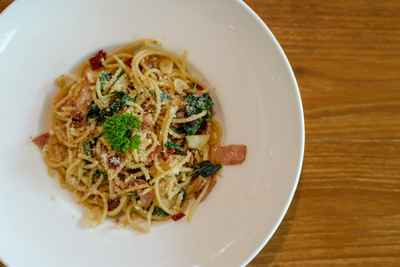 Top view of Delicious spicy spaghetti with bacon, dried chilli, basil and garlic