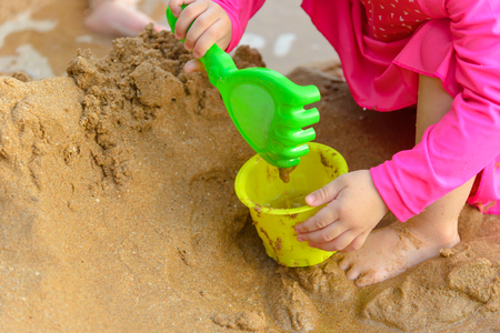 girl playing with shovel toys on the beach in summertime - childhood and summer concept