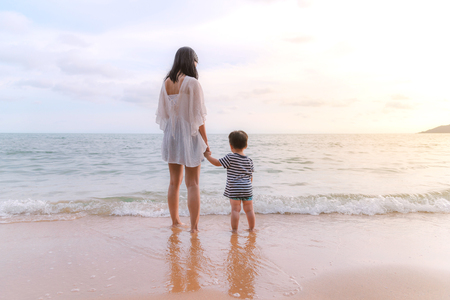 mother and son standing on the beach. Summer family vacation concept