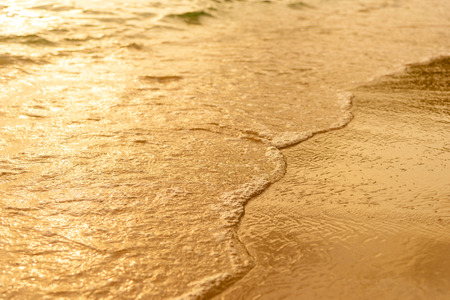 Golden light reflecting off a water wave at the sea and sand on sunset. Pure Gold 版權商用圖片