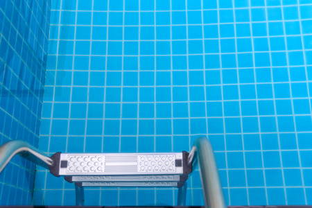 Metal ladder entrance to the swimming pool. Made of stainless steel Foto de archivo - 124774897