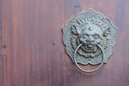 Antique chinese lion handle on wooden door. with copy space Reklamní fotografie - 124774900