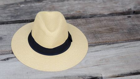 straw beach hat with black ribbon on the wooden seat wtih free space, travel summer concept Reklamní fotografie