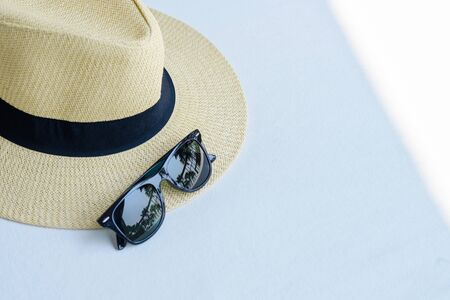 straw beach hat with black ribbon and sunglasses on the white table wtih free space, travel summer concept Reklamní fotografie