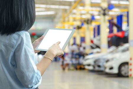 manager woman using a tablet pc with blur of auto repair service at garage