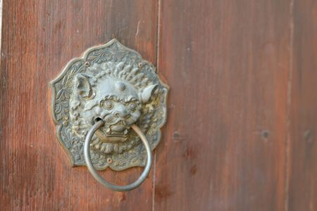 Antique chinese lion handle on wooden door. with copy space Banque d'images