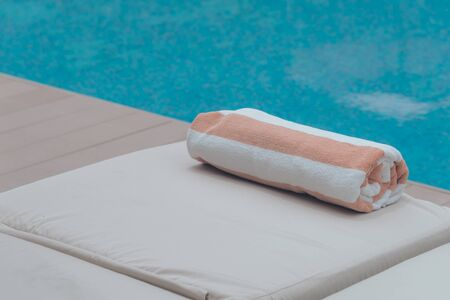 Roll soft towel on a sun bed near a swimming pool.