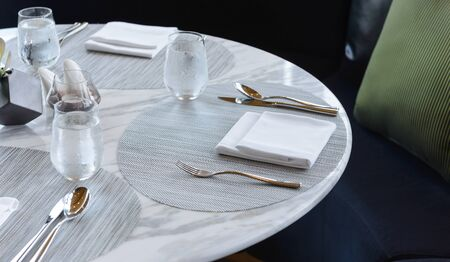 Table setting in the restaurant. Decorated elegant table, glasses, napkin, knife, fork and spoon Zdjęcie Seryjne