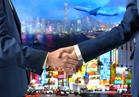 Double exposure of Businesspeople shaking hands with airplane flying, city and urban in the night as commitment. Business travel and transportation concept
