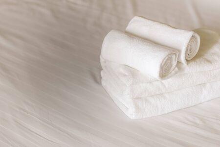 serviettes moelleuses blanches sur le lit dans la chambre d'hôtel. Vue rapprochée
