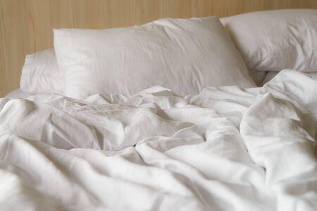 coperta bianca rugosa con morbidi cuscini sul letto comodo al mattino. incasinato dopo notti di sonno Archivio Fotografico
