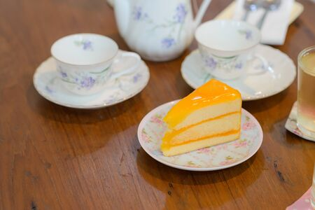 piece of delicious orange cake with teapot and cup of tea on wooden table Stock fotó