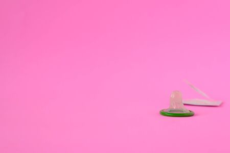 Green condom on pink paper background with copy space for text. Reproductive health and safe concept
