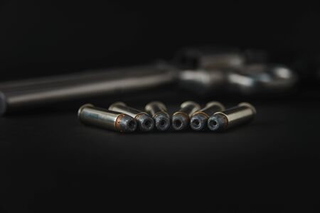 357 Caliber hollow point bullets near revolver pistol gun on black background