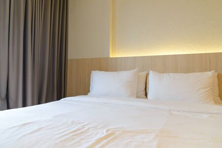 stacking of pillows on bed, white bed sheets with wooden bedhead