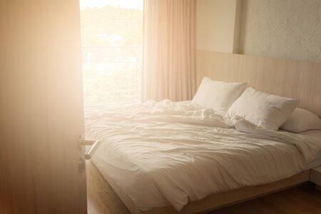 wrinkled white blanket with soft pillows on comfortable bed in the morning. messed up after nights sleep