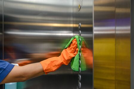 Woman hand in protective orange rubber gloves holding green microfiber cleaning cloth and wiping dust using a spray sterilizing solution make cleaning and disinfection for good hygiene