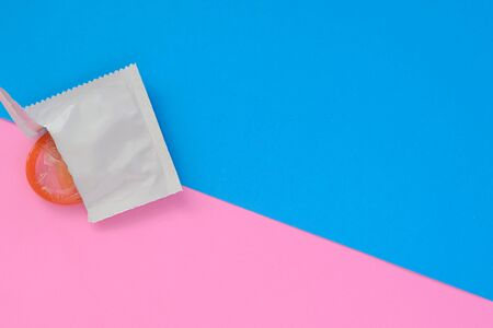 Top view of opened condom and red condom in pack on blue and pink color paper background with copy space for text. Reproductive health and safe sex concept Stock Photo