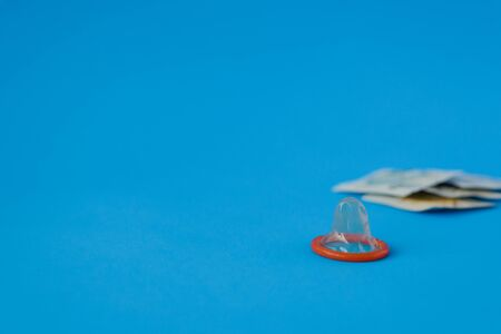 opened green condom with condom pack on blue paper background with copy space for text. Reproductive health, contraception and safe sex concept