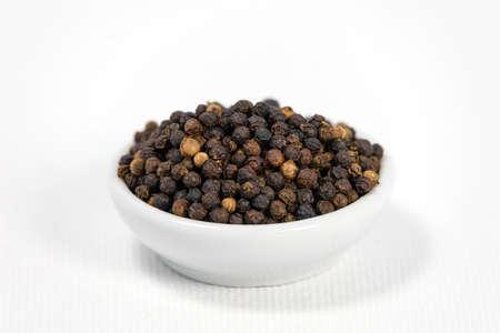 black pepper in white bowl on white canvas background 免版税图像
