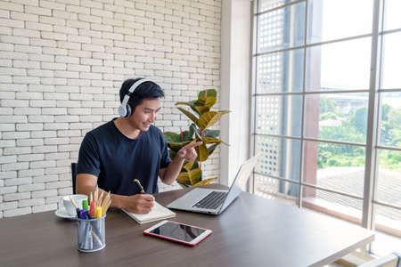 Smiling young asian man wear casual clothing while sitting at big wooden table in modern kitchen, working and video conference meeting from home with computer laptop at home - Social Distancing Concept Фото со стока