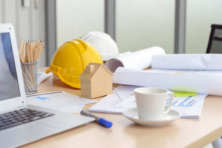 Hard safety helmet hat, construction equipment, blueprint on table in office worker conference site, architect working desk. Engineering tools concept
