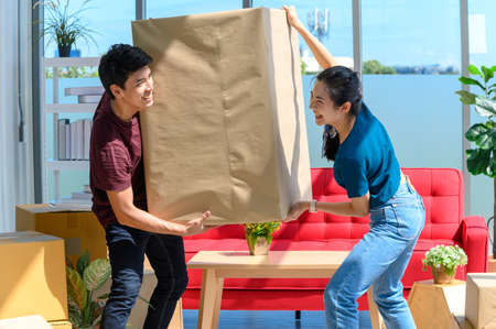young asian couple smiling and enjoy when they carrying big cardboard box while relocation into new home on moving day, celebrating moving to new home concept